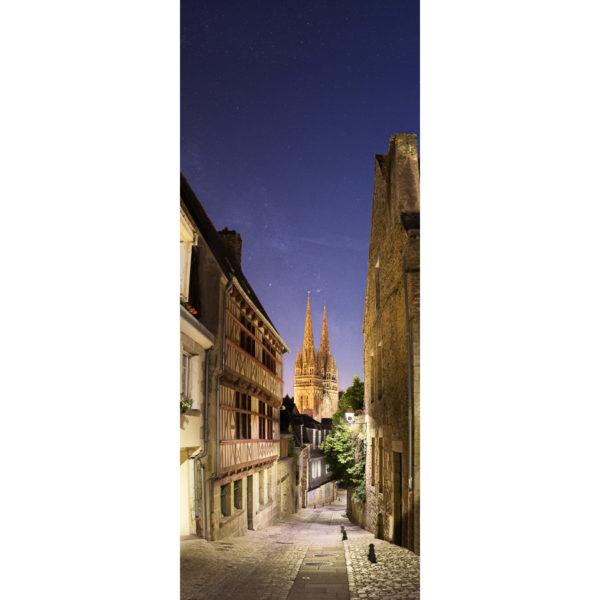 Depuis le haut de la rue du Lycée, la vue sur la cathédrale de Quimper est splendide. Les lampadaires bien conçus pour éclairer vers le bas permettent d'envisager de photographier la Voie lactée, malgré la présence de la Lune en Quartier qui teinte le ciel en bleu. J'ai dû composer différents temps de pose, de 1/15 s à 4 s pour capturer à la fois la rue éclairée et le ciel étoilé.