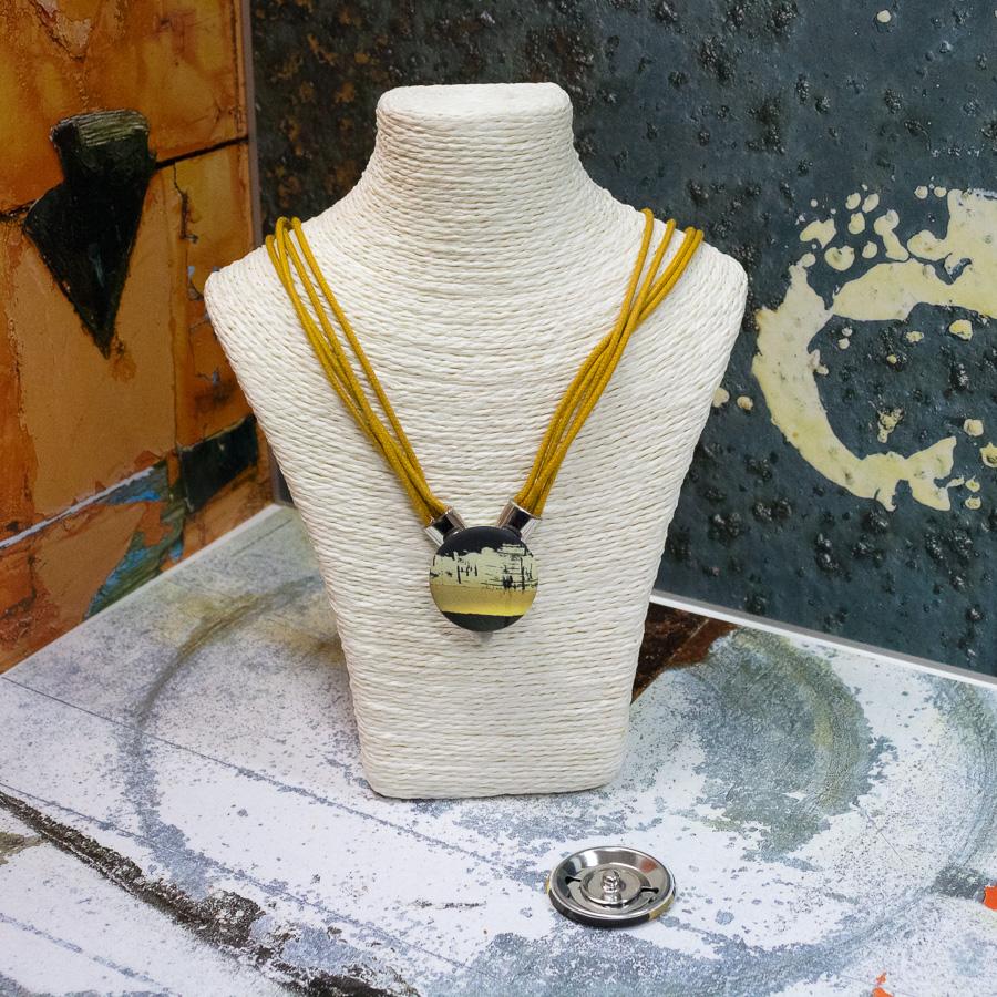 Collier composé de plusieurs cordons jaune avec fermoir aimanté sur le devant